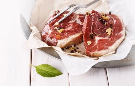 carne roja: La carne roja y el tenedor sobre fondo de madera blanca