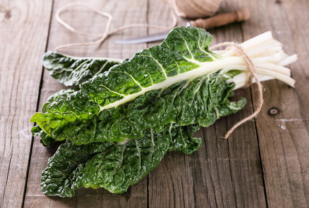 Bunch of organic silverbeet on a rustic wooden background. Selective focus, shallow depth of field