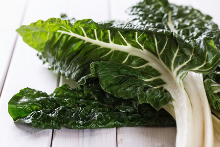 Bunch of organic silverbeet on a rustic wooden background. Selective focus, shallow dof