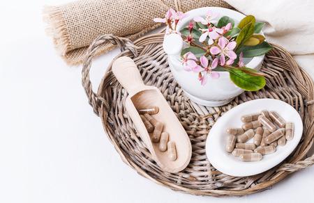 漢方薬の錠剤と白い背景で編まれたトレイにサンザシ花です。選択と集中、コピー スペース 写真素材