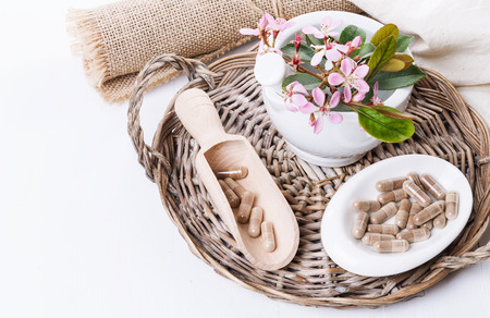 Herbal medicine pills and hawthorn flowers on a woven tray over white background. Selective focus, copy space Banco de Imagens
