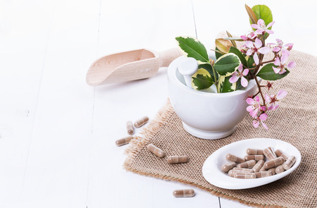 Herbal medicine pills and hawthorn flowers on a mortar over white background. Selective focus, copy space Banco de Imagens