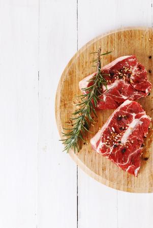 carnes rojas: La carne roja y romero sobre fondo de madera blanco con copia espacio. Vista superior Foto de archivo