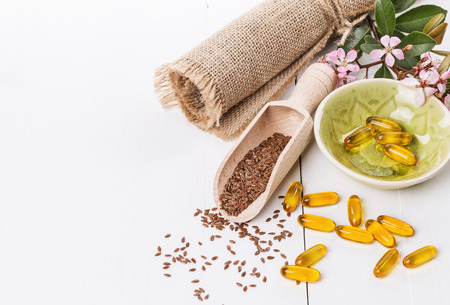 flaxseed: Linseed and flaxseed oil capsules over white wooden background with copy space