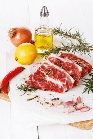 carnes rojas: Carnes rojas, especias y aceite sobre fondo de madera blanca