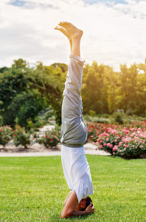 shirshasana: Yoga shirshasana headstand pose performed by man in sportswear in the park Stock Photo