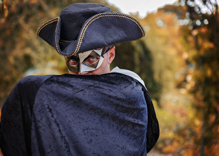 mystery man: Mystery man in masquerade mask, triangle hat and black velvet cape hiding his lower face with his hand. Autumn (fall) forest background, shallow depth of field