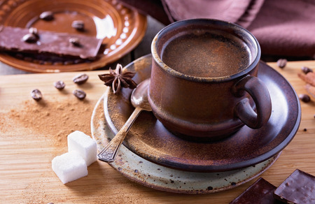anis: Spiced coffee in a textured ceramic cup with cinnamon powder, anis stars, sugar and pieces of chocolate over wooden table closeup. Selective focus, shallow depth of field