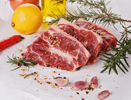 carne roja: Pedazos de �rboles de carne roja, verduras y hierbas sobre el fondo blanco