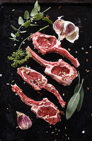 the lamb: Lamb cutlets with herbs on a black textured metal tray. Top view Stock Photo