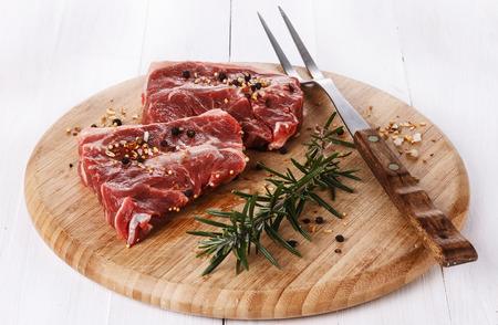 carnes rojas: Dos pedazos de la carne roja, el romero, especias y tenedor sobre una tabla de cortar redonda sobre blanco de madera. Copia espacio Foto de archivo