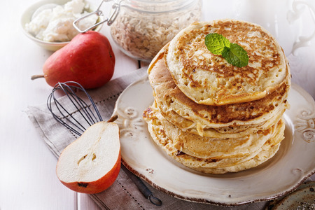 carbs: Stack of healthy low carbs oat pancakes over white wooden background Stock Photo