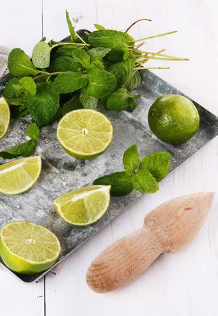 quarters: Limes halves and quarters and mint leaves in a vintage metal tray over rustic white wooden background. Selective focus