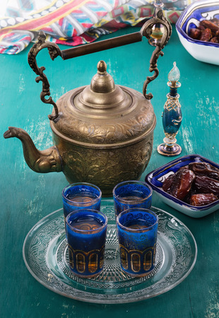 date palm: Middle Eastern tea and Ramadan date palm over turquoise wooden background