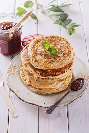carbs: Stack of healthy low carbs oat pancakes and jam over white wooden background Stock Photo