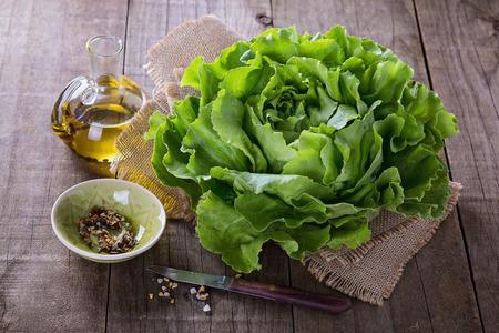 lechuga: Escoja la cabeza de lechuga mantequilla, aceite y condimentos sobre fondo de madera rústica