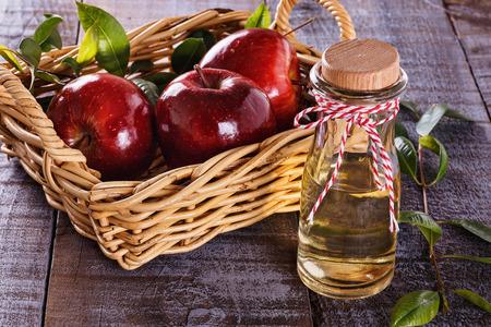 apfel: Apfelessig und rote Äpfel auf rustikalem Holzuntergrund