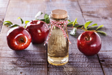 Le vinaigre de cidre et de pommes rouges sur fond de bois rustique