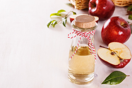 アップル サイダー酢と copyspace と白の木製の背景に赤いリンゴ。選択と集中