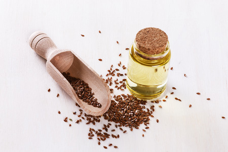 flaxseed: Linseed and bottled flaxseed oil over white wooden background