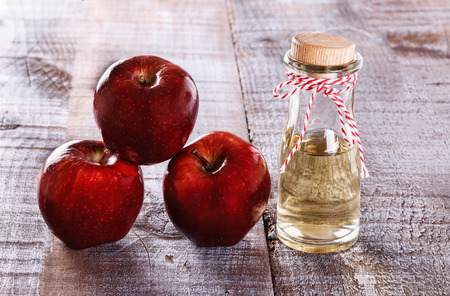food dressing: Apple cider vinegar and red apples over rustic wooden background. Selective focus