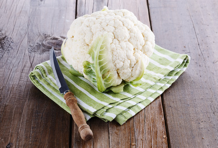 head of cauliflower: Single head of cauliflower and knife on a rustic wooden background