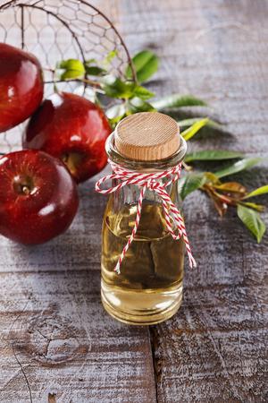 diet food: Apple cider vinegar and red apples over rustic wooden background. Selective focus