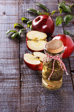 fresh: Apple cider vinegar and red apples over rustic wooden background. Selective focus