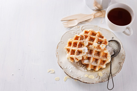 Homemade Belgian waffles dusted with icing sugar over white wooden background Banco de Imagens