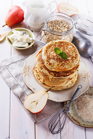 carbs: Breakfast concept. Stack of healthy low carbs oat pancakes with cottage cheese and fruits over white wooden background