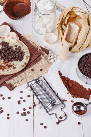 choc: Ingredients for baking with chocolate. Choc chips, cocoa powder, sugar cubes and flour over white wooden background Stock Photo