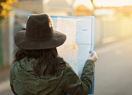 Travelling concept. Back view of a young girl in a khaki coat and hat looking at a map. Filters, color toning, selective focus, shallow depth of field, light leak, bokeh Banco de Imagens