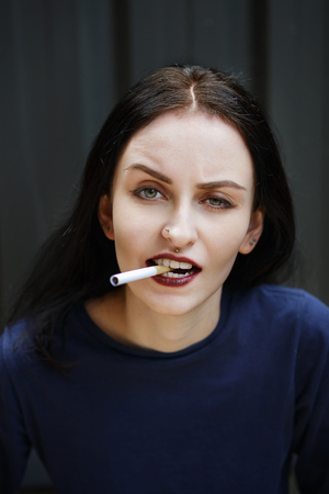 cynical: Cynical black-haired girl holding a cigarette between her teeth. Selective focus, shallow depth of field