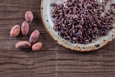Raw Cacao Nibs in a ceramic plate and cacao beans over rustic wooden background. Top view