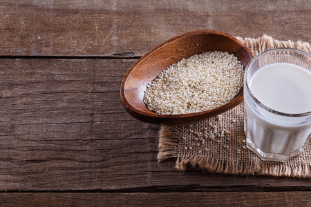 sesame seed: Glass of sesame seed and seeds in a wooden bowl over rustic wooden background with copy space