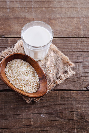 preservatives: Glass of sesame seed milk and seeds in a wooden bowl over rustic wooden background Stock Photo