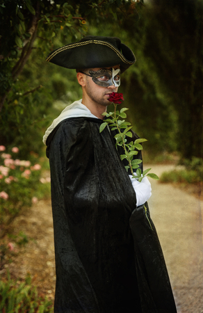 romantic man: Retro image of romantic mystery man in black mask and velvet cape holding a red rose. Selective focus, Color toning, Filters, Aging effects