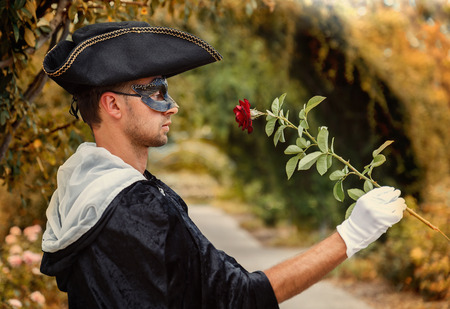 mystery man: Romantic mystery man in black mask and velvet cape holding a red rose. Selective focus