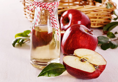 enzymes: Apple cider vinegar and red apples over rustic wooden background. Selective focus