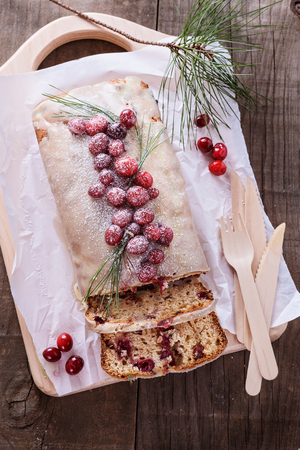 pound cake: Cranberry pound cake with two slices and fresh cranberries over rustic wooden background Stock Photo