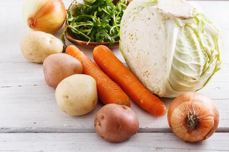白い木製のテーブルで生の有機冬野菜をクローズ アップ