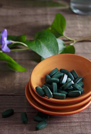 Spirulina pills in a ceramic plate over wooden rustic background Banco de Imagens