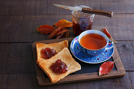 bl: Cup of tea, two toasts, jar of jam and red leaves over rustic wooden background
