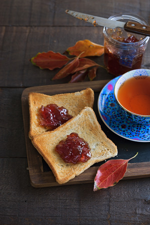 bl: looking picture of cup of tea, two toasts, jar of jam and red leaves over rustic wooden background. Color toning, lifted shadows Stock Photo
