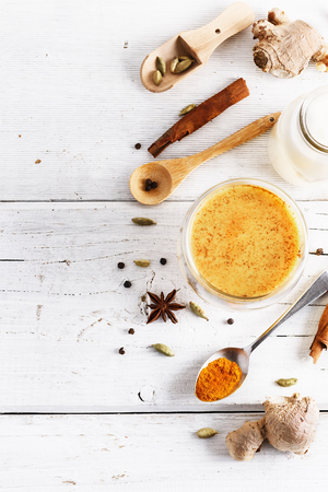 Top view image of turmeric latte and spices with copyspace