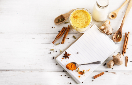 Golden turmeric latte in a glass, spices and recipe book over white wooden background with copy space Stock Photo