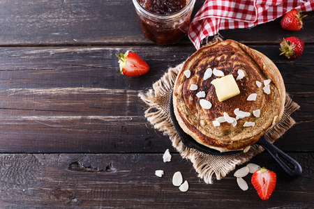 Pancakes, strawberries and jam over dark rustic wooden background close up. Top view