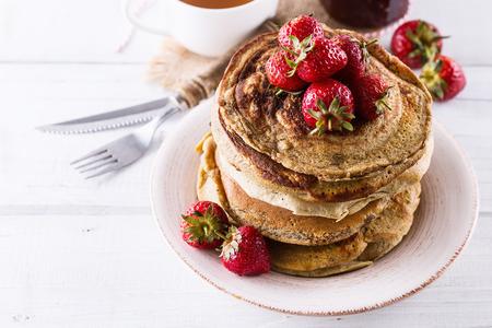 パンケーキと木製の白い背景の上のイチゴをクローズ アップ