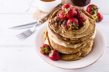 Pancakes and strawberries over white wooden background close up