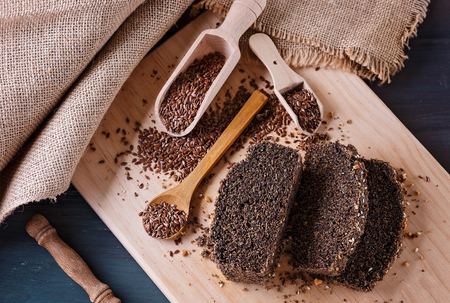 Grain free flaxseed bread slices on a cutting board over rustic wooden background. Close up Stock Photo